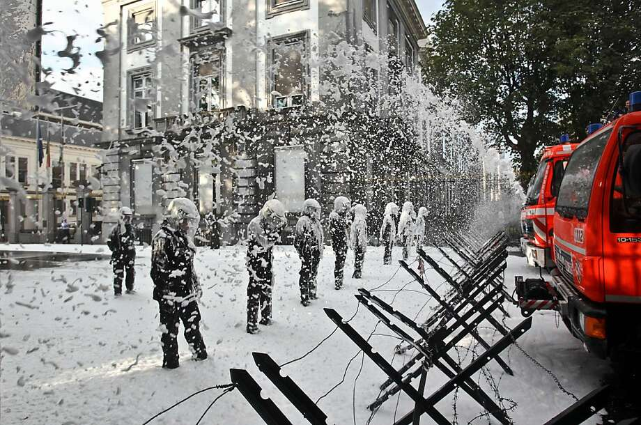 We need more money for foam:Firefighters spray foam on riot police from behind barricades during a protest near 