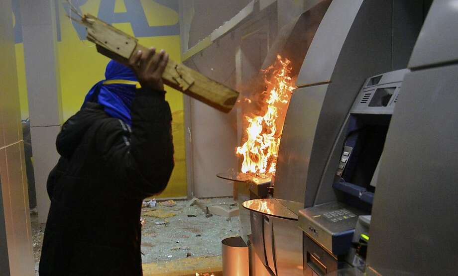 Probably not a teacher: A masked vandal smashes and burns ATM machines following a peaceful 