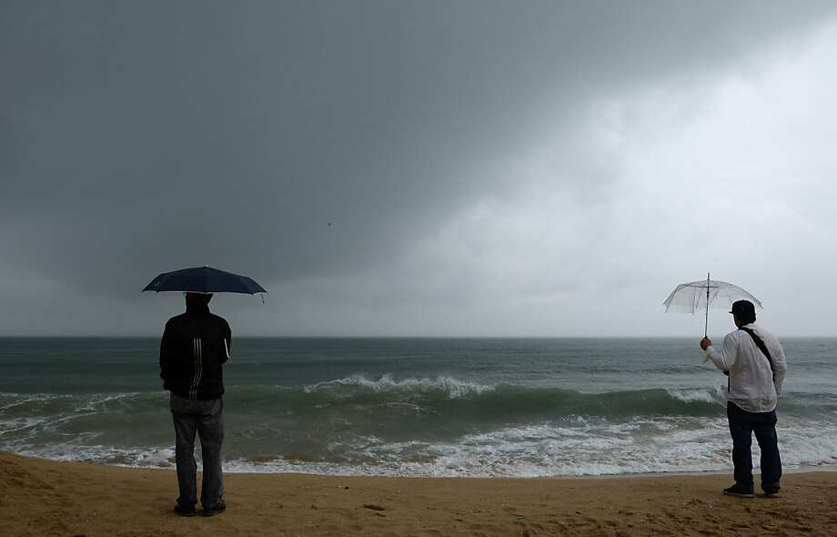 Storm's coming: Two men watch the horizon along Haeundae beach in Busan, South Korea, ahead of the expected 