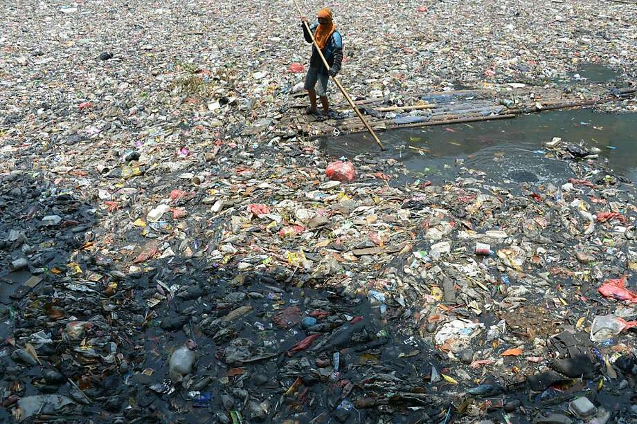 "The worst job in Jakarta - river cleaner: According to the AFP caption, this worker is ""cleaning"" a river in 