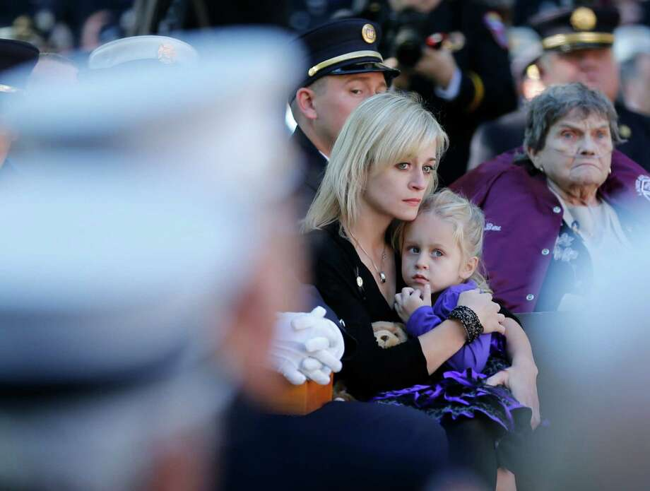 Kimberly Chiapperini holds her daughter Kylie during a ceremony at the New York State Fallen Firefighters Memorial on Tuesday, Oct. 8, 2013, in Albany, N.Y. Chiapperini's husband Michael was one of two West Webster Fire Department members whose names were added to the memorial during a ceremony honoring firefighters who died in the line of duty. The West Webster firefighters were killed in a Christmas Eve ambush last year. (AP Photo/Mike Groll) ORG XMIT: NYMG102 Photo: Mike Groll, AP / AP