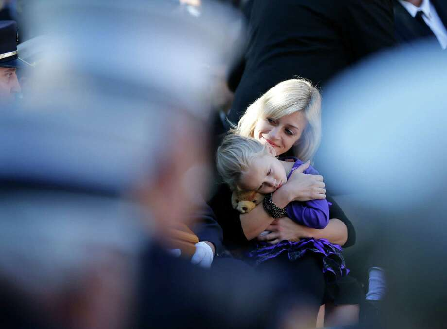 Kimberly Chiapperini holds her daughter Kylie during a ceremony at the New York State Fallen Firefighters Memorial on Tuesday, Oct. 8, 2013, in Albany, N.Y. Chiapperini's husband Michael was one of two West Webster Fire Department members whose names were added to the memorial during a ceremony honoring firefighters who died in the line of duty. The West Webster firefighters were killed in a Christmas Eve ambush last year. (AP Photo/Mike Groll) ORG XMIT: NYMG101 Photo: Mike Groll, AP / AP