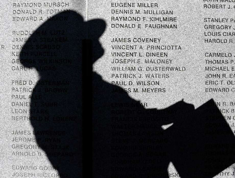 A firefighter waits to make a rubbing of a name on the New York State Fallen Firefighters Memorial on Tuesday, Oct. 8, 2013, in Albany, N.Y. Nine names, including two suburban Rochester volunteer firefighters killed in a Christmas Eve ambush, were added to the wall. (AP Photo/Mike Groll) ORG XMIT: NYMG104 Photo: Mike Groll, AP / AP