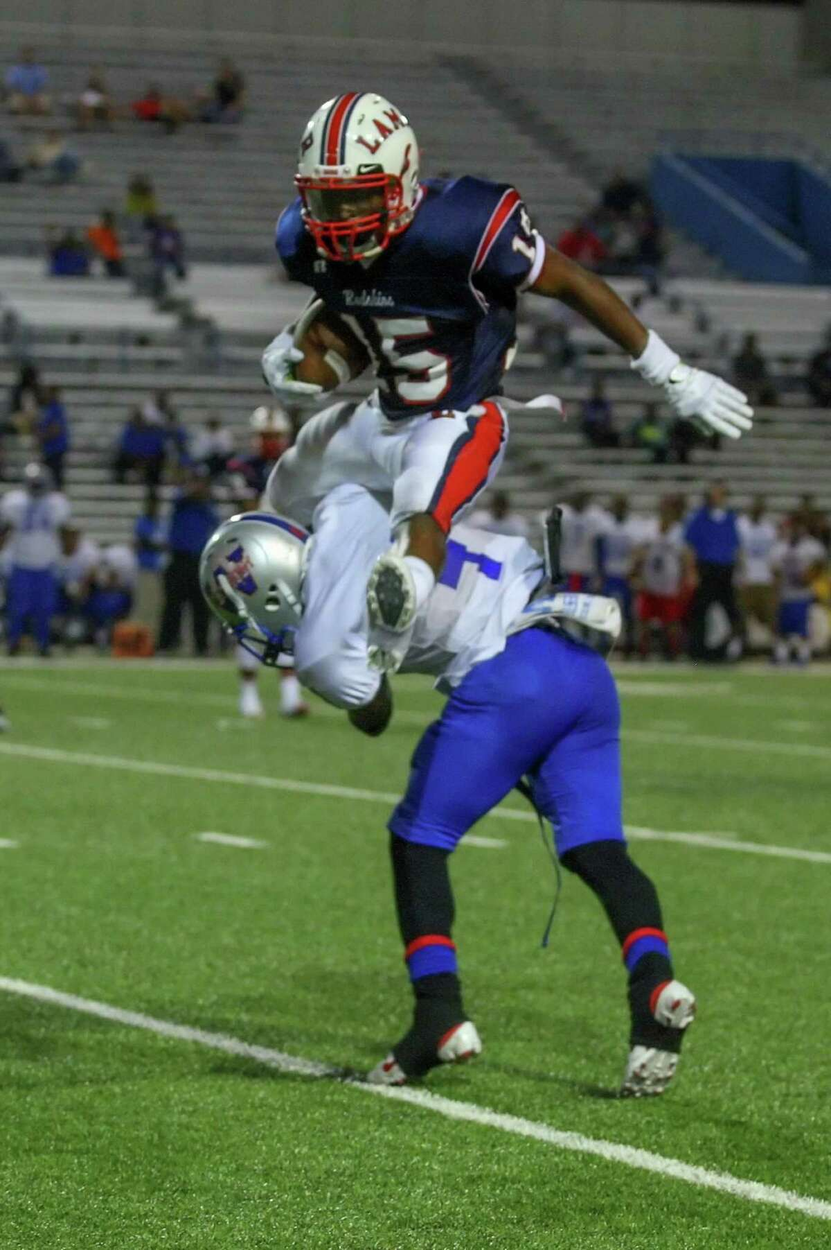 Lamar running back Ivy Smith leaps over Westbury defensive back Tydarian Jones to avoid a tackle attempt.