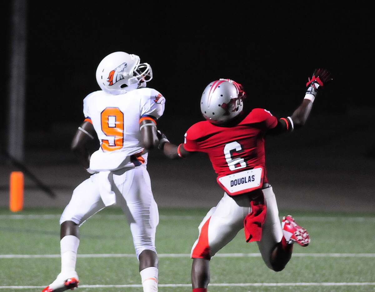 Bush wide receiver Kasey Poole (#9) goes downfield as Travis defensive back Jordan Haynes (#6) covers him during their game at Mercer Stadium Friday 10/04/13.