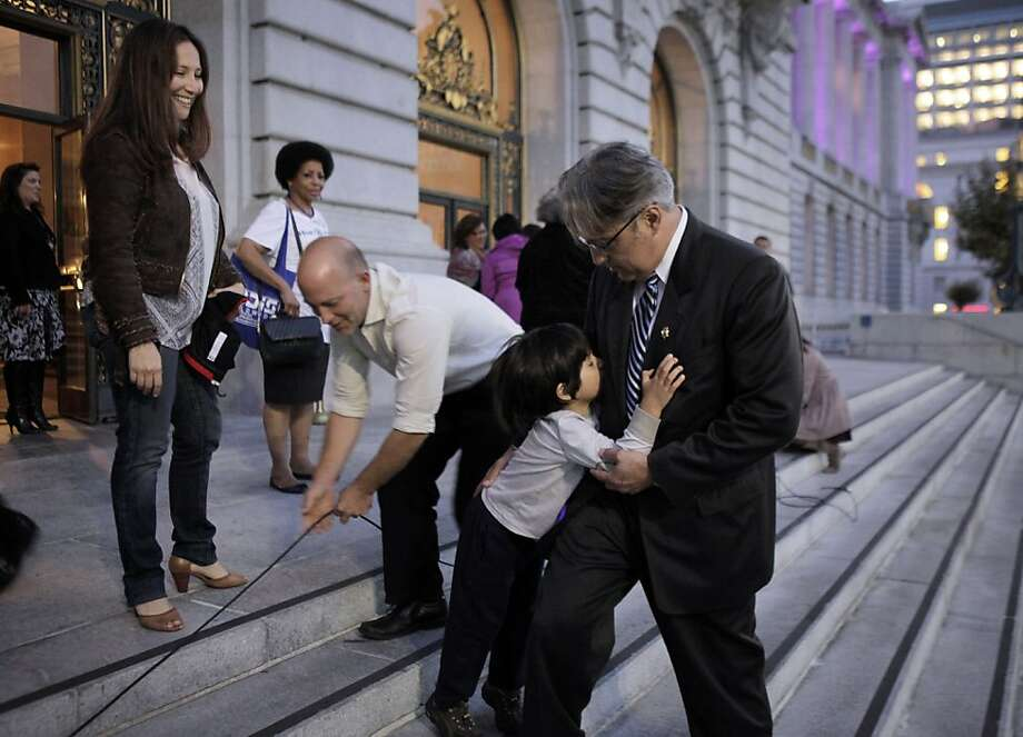 Theo Mirkarimi, 4, son of Sheriff Ross Mirkarimi, jumps up against his father as crews break down the podium and his mother watches after a domestic violence rally at City Hall. Photo: Carlos Avila Gonzalez, The Chronicle