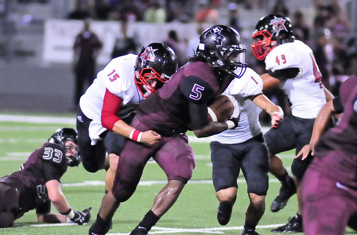 George Ranch running back Xavian Marks (5) advances the ball as he is grabbed by Terry linebacker Jeremy Arriaga (15) during the Longhorns' 33-14 win.