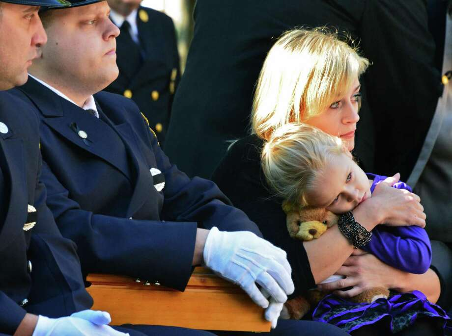 Kim Chiapperini, widow of Michael Chiapperini, who was killed when firefighters were ambushed as they responded to a call in Webster, NY,   holds daughter Kylie, 3, during the 16th Annual New York State Fallen Firefighters Memorial Ceremony at the Empire State Plaza on Tuesday, Oct. 8, 2013, in Albany, NY.   (John Carl D'Annibale / Times Union) Photo: John Carl D'Annibale / 00023755A