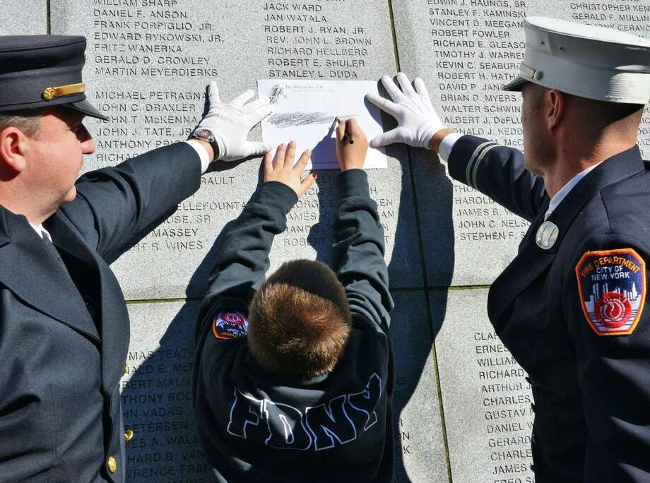 Aided by NYS Fire's Andy Joenes, left, and FDNY Capt. Joeseph Sweeney, Nickolas Nappi takes a rubbing of the name of his father, New York City Fire Department Lt. Richard A. Nappi, during the 16th Annual New York State Fallen Firefighters Memorial Ceremony at the Empire State Plaza on Tuesday, Oct. 8, 2013, in Albany, NY.   (John Carl D'Annibale / Times Union) Photo: John Carl D'Annibale / 00023755A