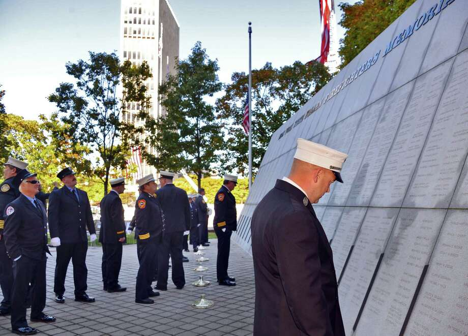 FDNY Lt. Robert Lee, at right, looks at the names on the memorial before the start of the 16th Annual New York State Fallen Firefighters Memorial Ceremony at the Empire State Plaza on Tuesday, Oct. 8, 2013, in Albany, NY.   (John Carl D'Annibale / Times Union) Photo: John Carl D'Annibale / 00023755A