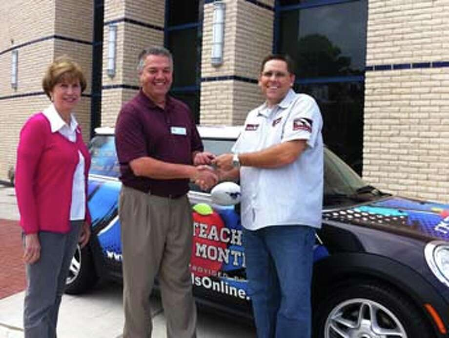 Kay Tucker stands with Scott Cobb of Motor Trends as he hands over the keys to a decorated Mini Cooper to Friendswood High School Teacher of the Year Paul Tucker. Photo: Provided By Friendswood High School