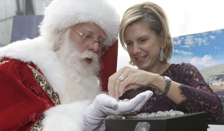 Jewelry designer Maria Canale hands Santa Claus loose diamonds offered in the Neiman Marcus Christmas Book. Photo: LM Otero, Associated Press