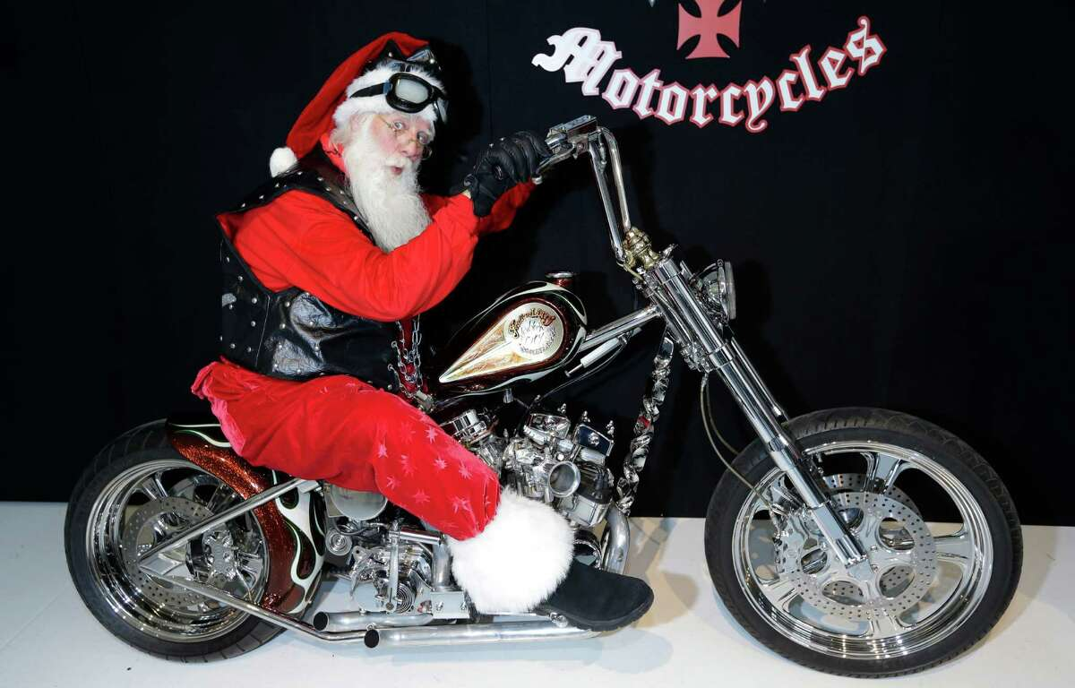 """Actor Brady White portrays Santa Claus as he sits atop the Indian Larry's """"Wild Child"""" Motorcycle during the unveiling of the gifts included in the Neiman Marcus Christmas Book Tuesday, Oct. 8, 2013, in Dallas. Hand built in Brooklyn, the bike is on sale for $750,000. (AP Photo/LM Otero)"""