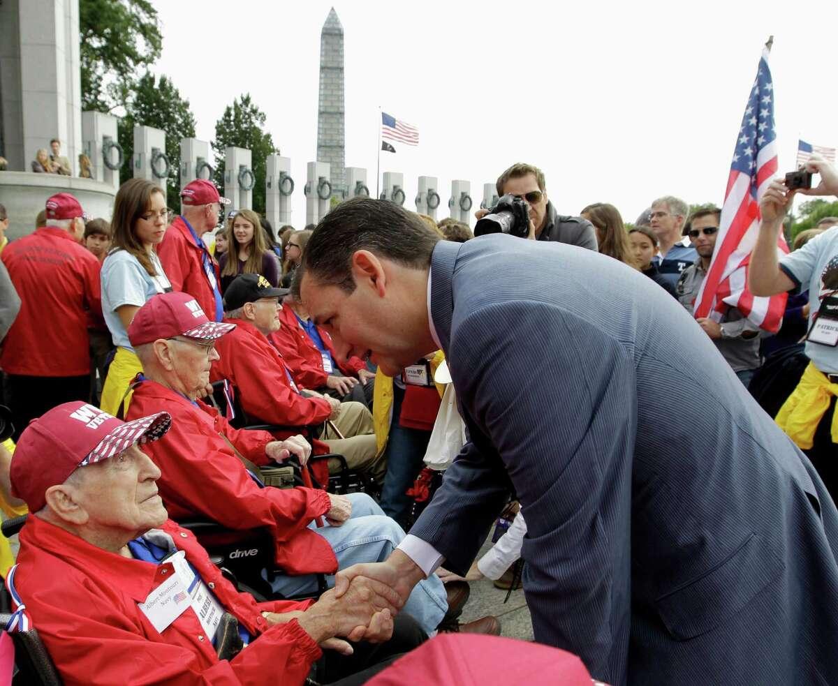 Sen. Ted Cruz, R-Texas, talks to U.S. Navy World War II veteran Albert Montouri, of Texas, during a visit at the World War II Memorial in Washington, Tuesday, Oct. 8, 2013.