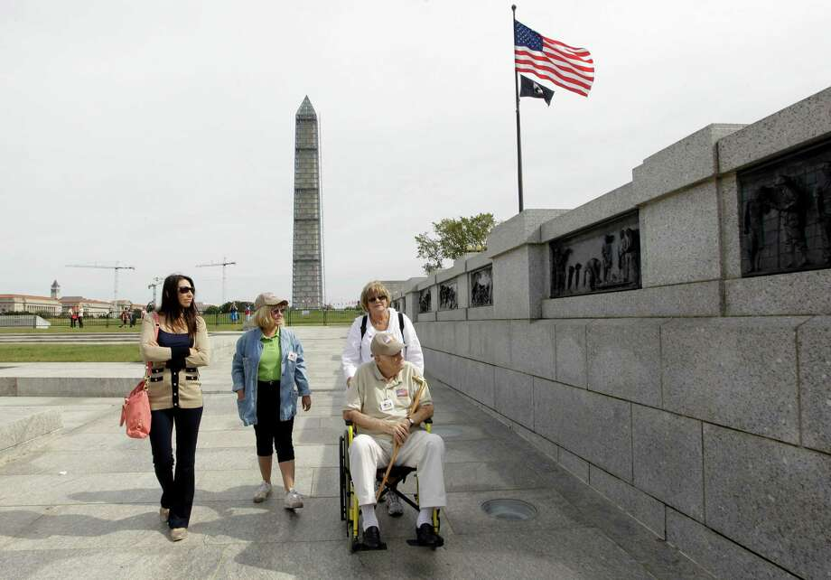 Carol Reiser, left, Joanne Abbate, center, and Joyce Millar, right, escort U.S. Army World War II veteran Witty Wald, of Florida, through a section of the World War II memorial in Washington, Tuesday, Oct. 8, 2013. Photo: Luis M. Alvarez, Associated Press / FR596 AP