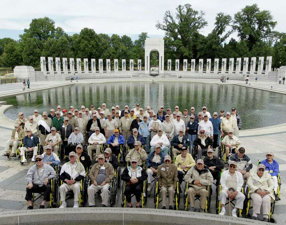 A group of World War II veterans from Florida pose for a photo during their visit to the World War II memorial in Washington, Tuesday, Oct. 8, 2013. Photo: Luis M. Alvarez, Associated Press / FR596 AP