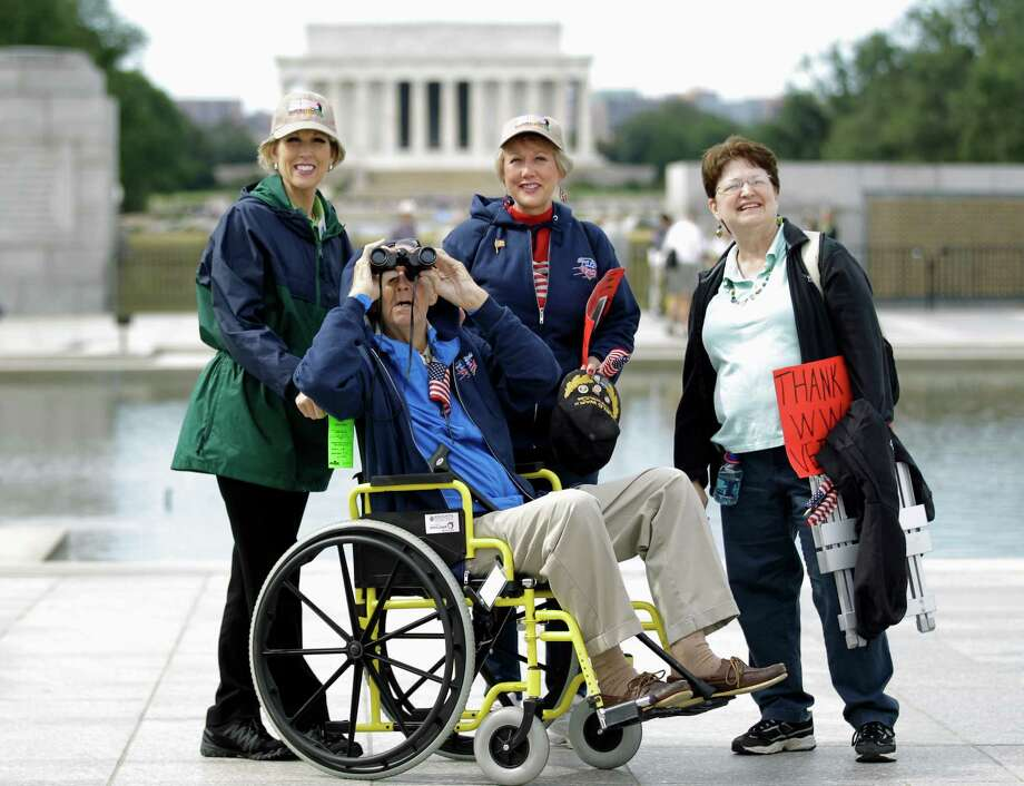 World War II veteran Marvin Bruning, front center, looks at the Washington Monument,accompanied by his daughters, Connie Bruning, left, Carol Butts, center, and friend Gloria Price, right,  during a visit at the World War II Memorial in Washington, Tuesday, Oct. 8, 2013. The Lincoln Memorial is in the background. Photo: Luis M. Alvarez, Associated Press / FR596 AP