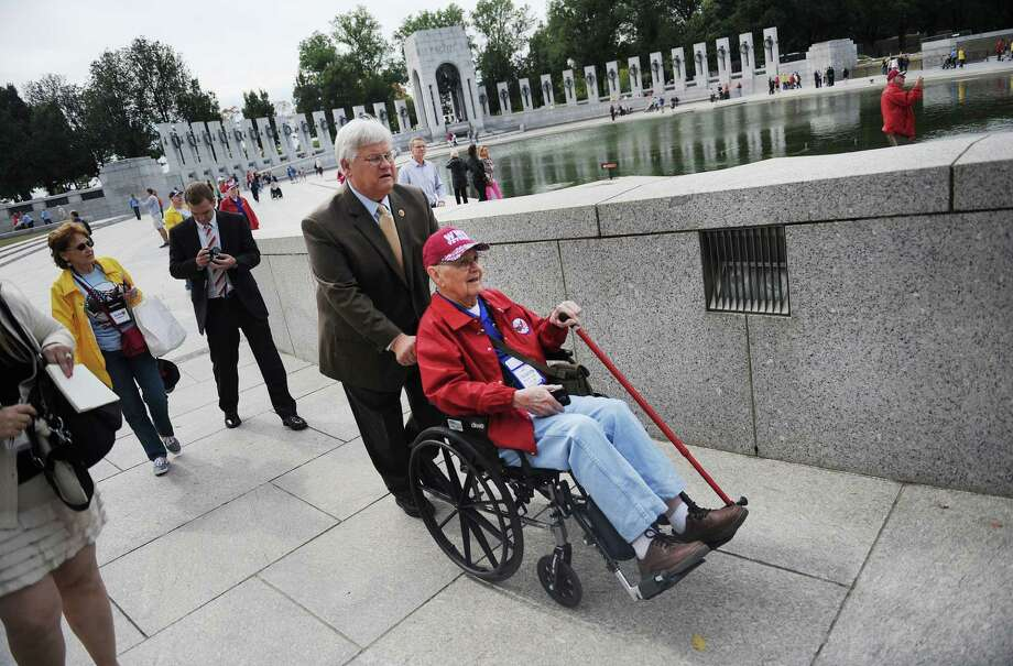 Congressman Kenny Marchant (R-TX) helps push WWII veteran Charles Vermillion from Texas at the WWII Memorial in Washington, D.C., October 8, 2013. Photo: Olivier Douliery, McClatchy-Tribune News Service / Abaca Press