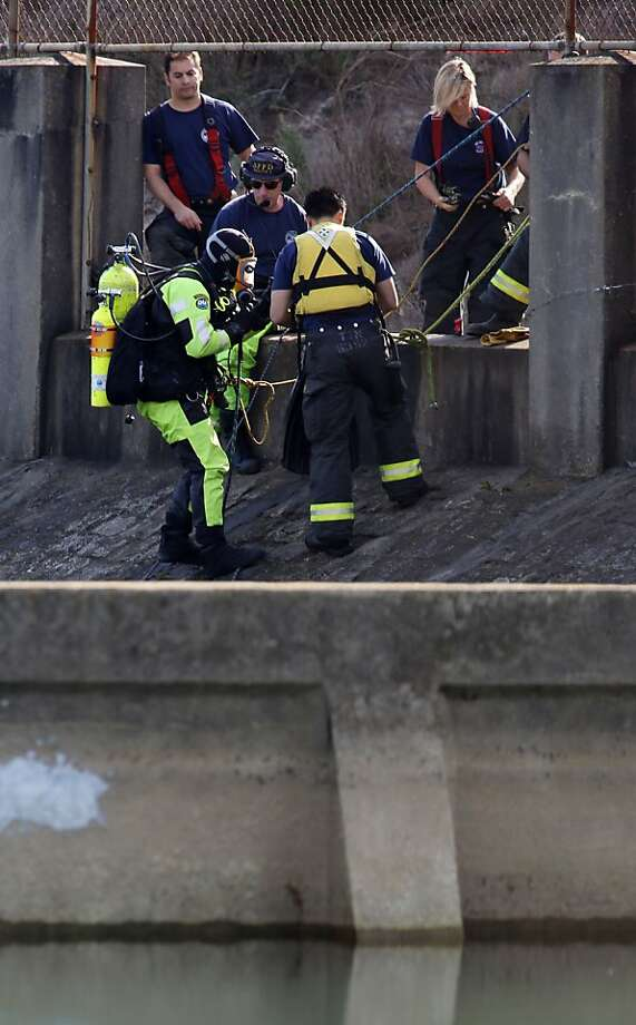 A fire department diver enter the Twin Peaks Reservoir in search of the driver of a vehicle that crashed after it went off the roadway on Twin Peaks Blvd. early Tuesday morning Oct. 8, 2013, in San Francisco. Photo: Mathew Sumner, Special To The Chronicle