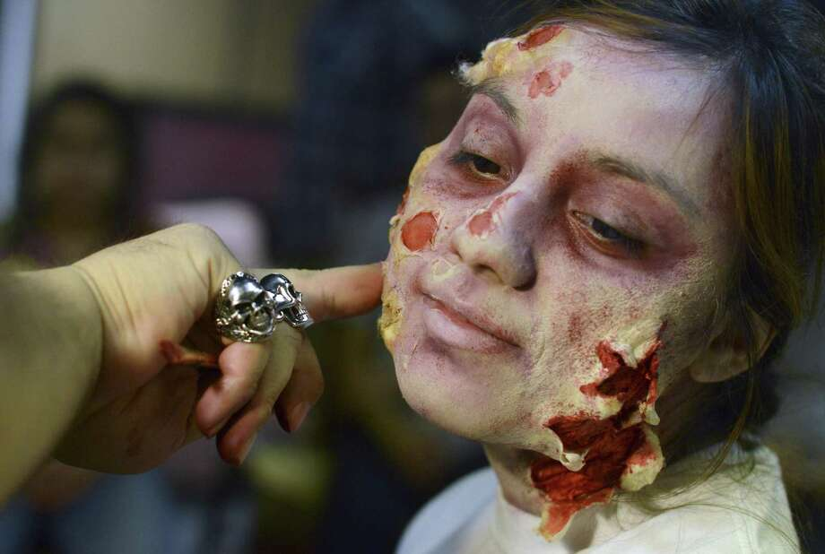 Kayla Yepez wears zombie makeup applied by Sergio Guerra during a zombie makeup workshop at the Overtime Theater. Photo: Billy Calzada / San Antonio Express-News