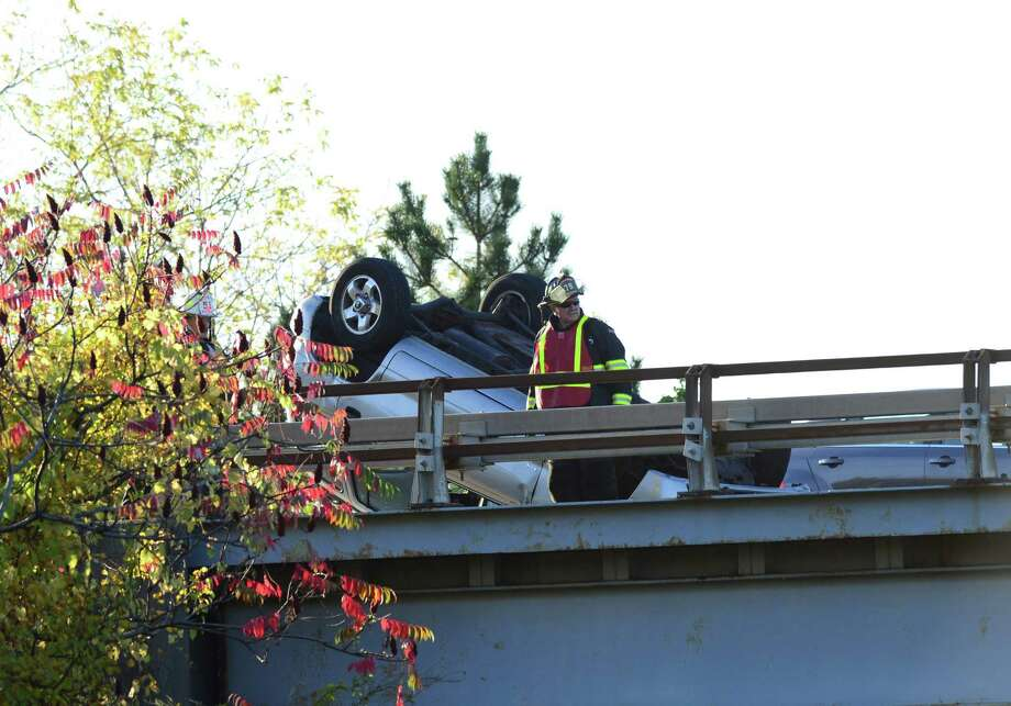 Emergency personnel attend to a vehicle which was flipped onto its roof Tuesday evening, Oct. 8, 2013, in the northbound lanes of the Northway at Albany-Shaker Rd. in Colonie, N.Y. (Will Waldron/Times Union) Photo: WW