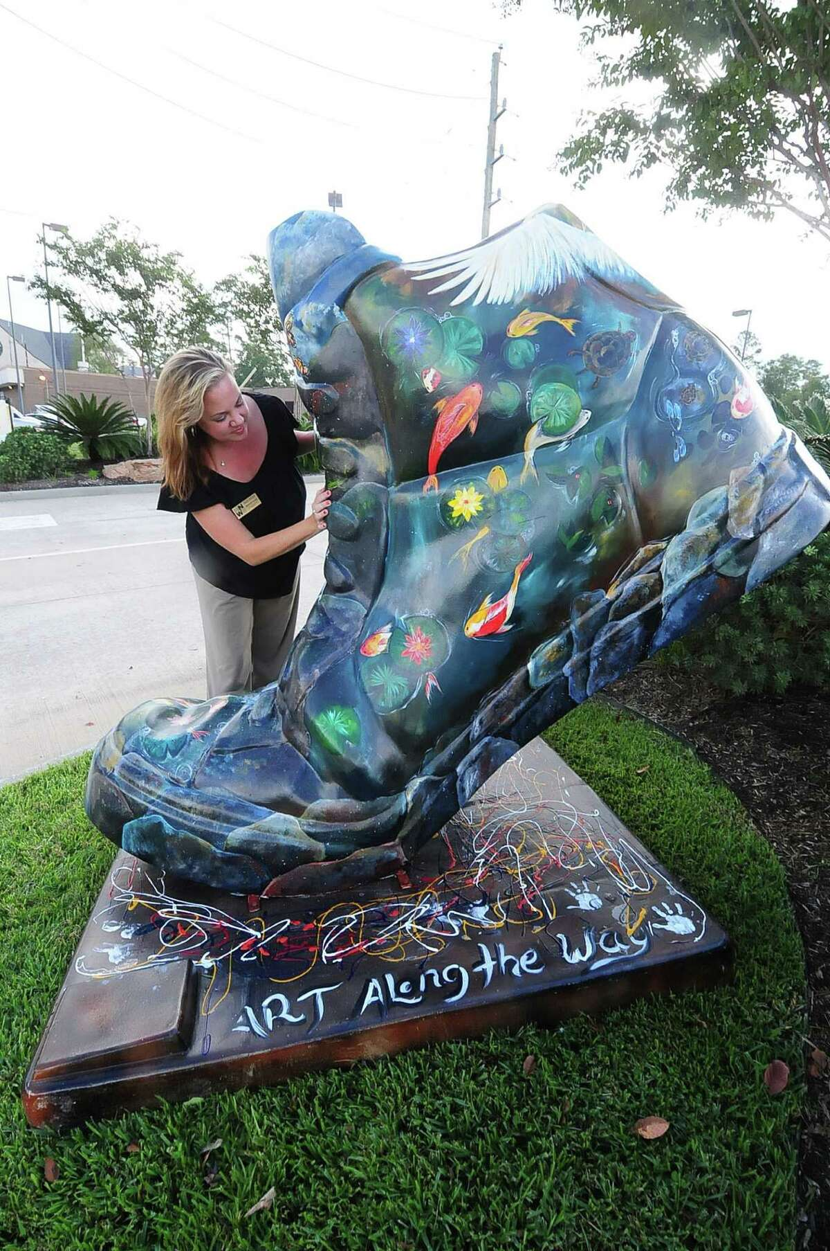 Meredith Brown, Northwest Area Chamber, examines an art piece promoting the Creek Fest event set for Oct. 12.