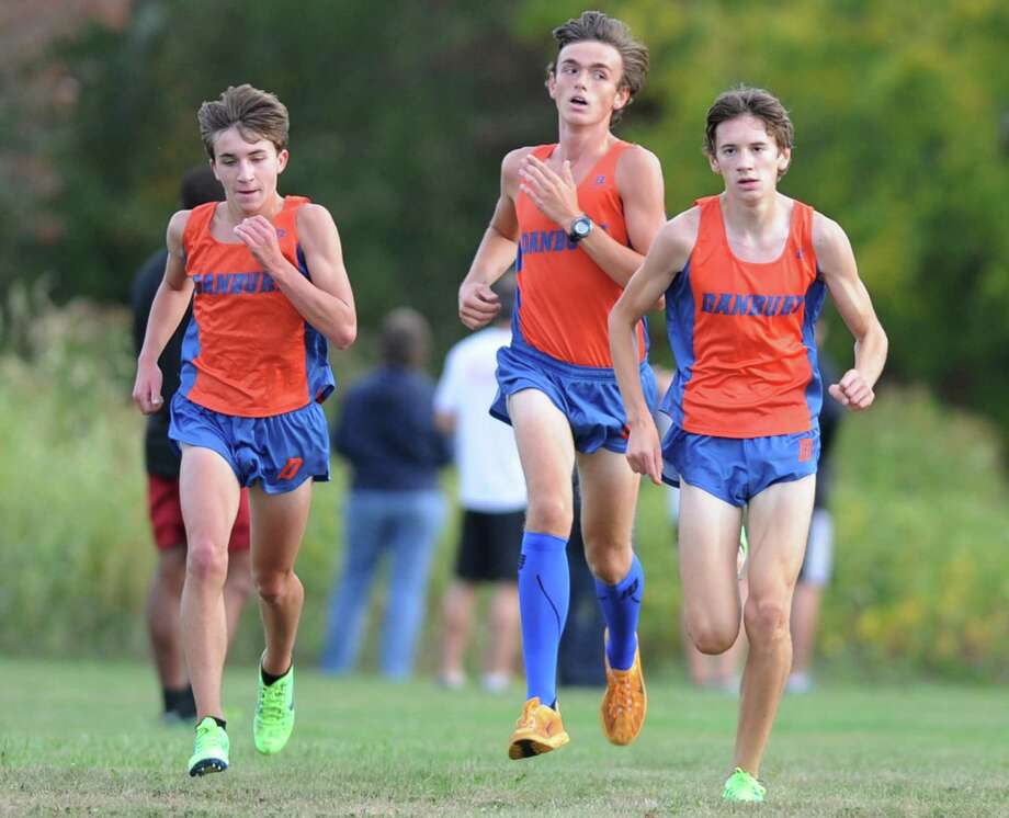 Danbury runners, from left, Ryan Ansel, Eric Waterman and Corey Mullins, runs down the final stretch in the FCIAC high school cross country meet between New Canaan, Danbury, Ridgefield, St. Joesph and Trinity Catholic at the Waveny Park course in New Canaan, Conn. on Tuesday, Oct. 8, 2013.  Mullins finished third, Ansel fourth and Waterman fifth, helping the Danbury boys team sweep the competition.  The 4-0 performance Tuesday put the team over the 800 win mark. Photo: Tyler Sizemore / The News-Times