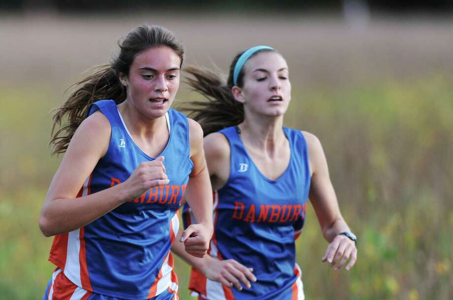 Danbury's Sarah Krate, left, and Brittany Kenyon battle down the final stretch at the FCIAC high school cross country meet between New Canaan, Danbury, Ridgefield, St. Joesph and Trinity Catholic at the Waveny Park course in New Canaan, Conn. on Tuesday, Oct. 8, 2013.  Krate finished fifth overall with a time of 16:26 and Kenyon finished seventh with a time of 16:33. Photo: Tyler Sizemore / The News-Times