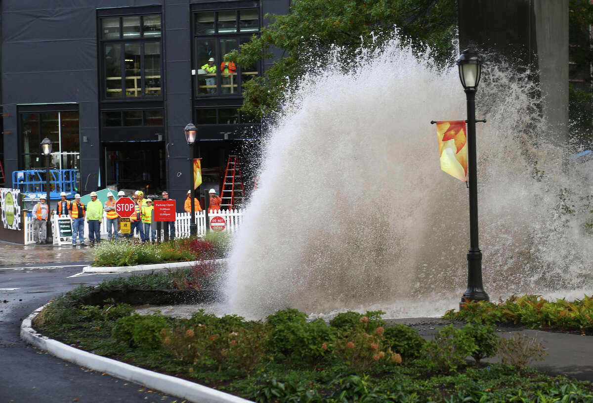 Water erupts from the ground after a main burst under the NE 45th Street Viaduct, flooding the streets of University Village on Tuesday, October 8, 2013. Stores and businesses in the popular shopping destination were spared from the flood of water. There was concern that the flood of water may have undermined the support structures of the bridge.