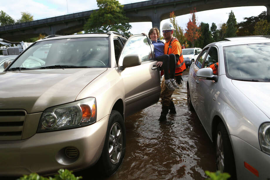 Syrian Seth carries a customer to her car after a water main burst under the NE 45th Street Viaduct, flooding the streets of University Village on Tuesday, October 8, 2013. Stores and businesses in the popular shopping destination were spared from the flood of water. There was concern that the flood of water may have undermined the support structures of the bridge. Photo: JOSHUA TRUJILLO, SEATTLEPI.COM / SEATTLEPI.COM