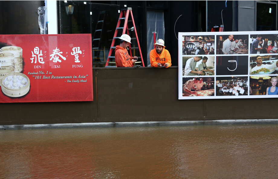 Construction workers watch a river of water after a water main burst under the NE 45th Street Viaduct, flooding the streets of University Village on Tuesday, October 8, 2013. Stores and businesses in the popular shopping destination were spared from the flood of water. There was concern that the flood of water may have undermined the support structures of the bridge. Photo: JOSHUA TRUJILLO, SEATTLEPI.COM / SEATTLEPI.COM