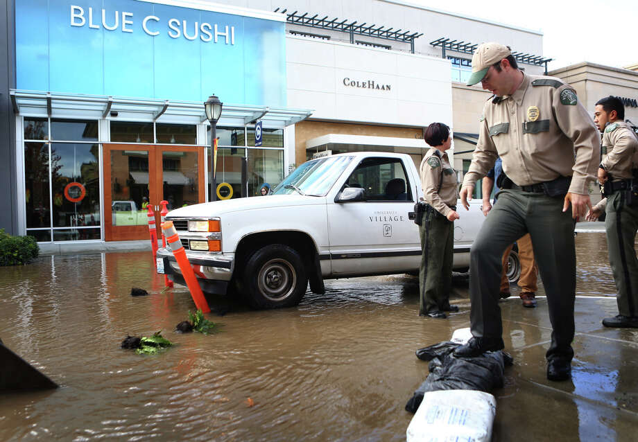 Security officers place sandbags after a water main burst under the NE 45th Street Viaduct, flooding the streets of University Village on Tuesday, October 8, 2013. Stores and businesses in the popular shopping destination were spared from the flood of water. There was concern that the flood of water may have undermined the support structures of the bridge. Photo: JOSHUA TRUJILLO, SEATTLEPI.COM / SEATTLEPI.COM