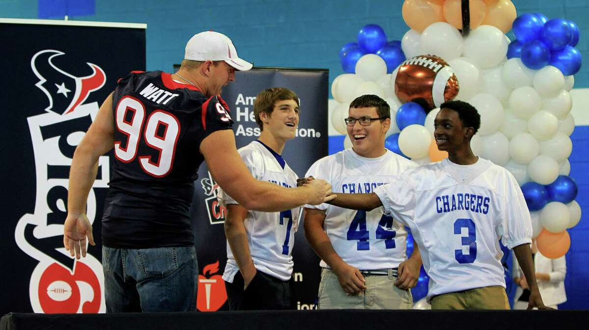 Houston Texans defensive end J. J. Watt high fives football players Enan Williform,(#3), Johnathan Hernandez (#44) and Christian Cherry (#7) after they won a round playing