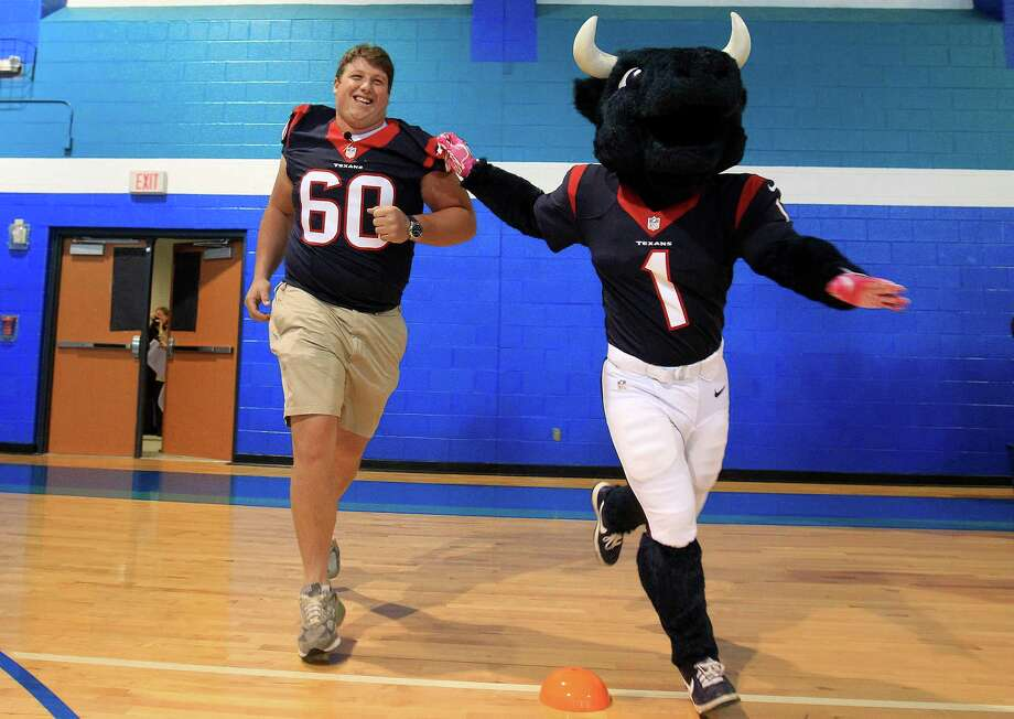 Toro the Houston Texans mascot runs out with offensive end Ben Jones into a pep rally as the Texans and the American Heart Association kicked off the NFL PLAY 60 Challenge with more than 1,000 students at Pin Oak Middle School. Photo: Karen Warren, Houston Chronicle / © 2013 Houston Chronicle