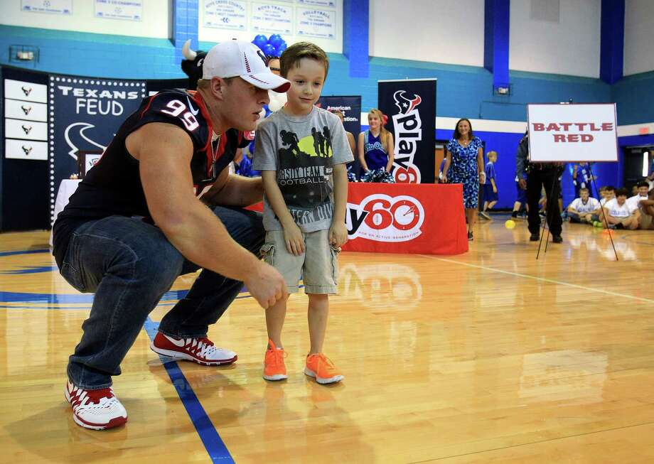 Houston Texans defensive end J. J. Watt chats with Donovan Wagers, 5, during a pep rally. Photo: Karen Warren, Houston Chronicle / © 2013 Houston Chronicle