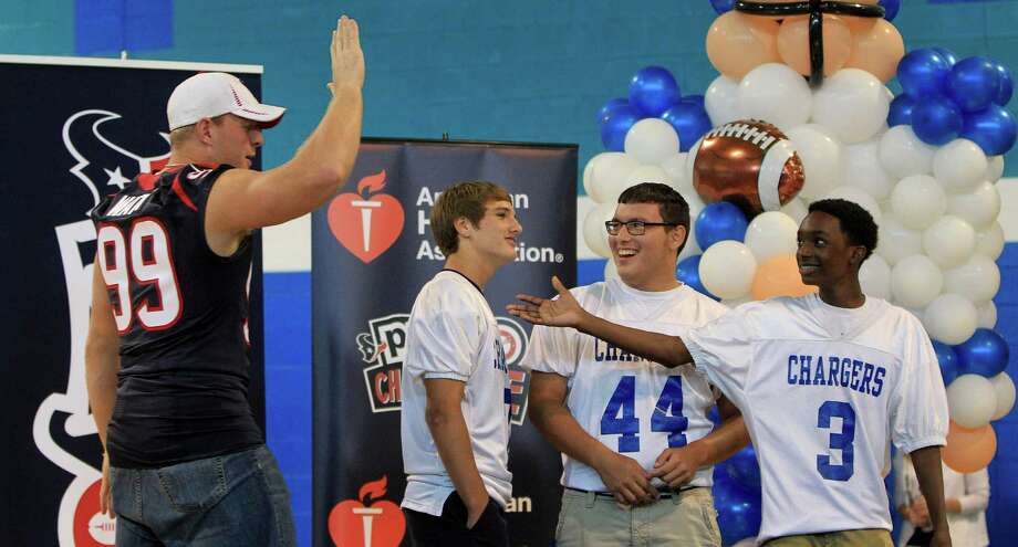 "Houston Texans defensive end J. J. Watt high fives football players  Enan Williform,(#3), Johnathan Hernandez (#44) and Christian Cherry (#7) after they won a round playing ""Texans Feud"", a game show focused on health and nutrition facts as they kicked off the NFL PLAY 60 Challenge. Photo: Karen Warren, Houston Chronicle / © 2013 Houston Chronicle"