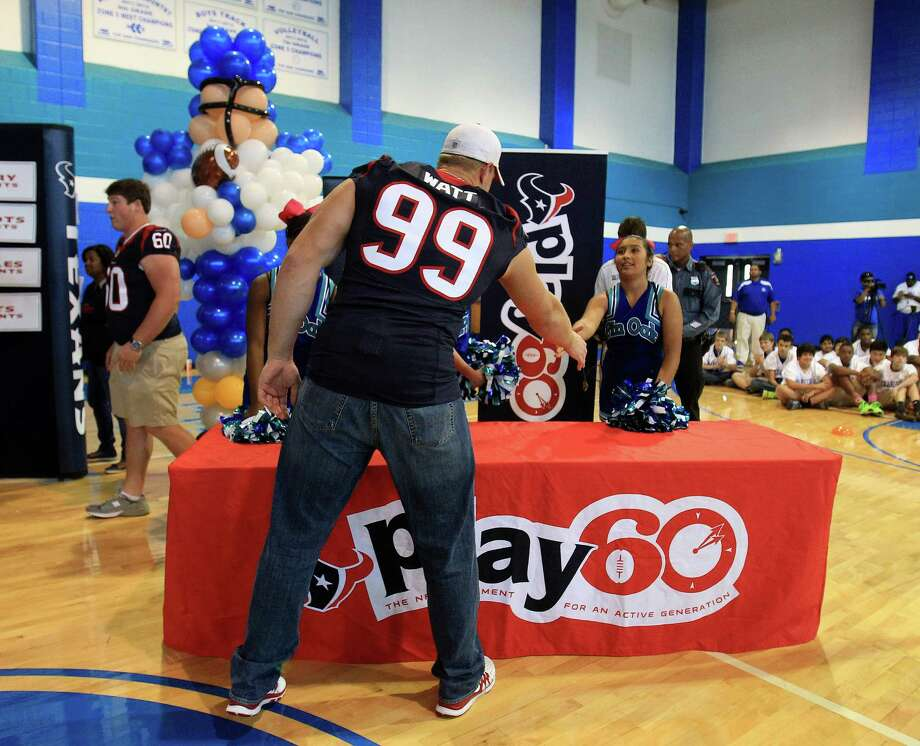 Houston Texans defensive end J. J. Watt shakes hands with eighth-grader Sabrina Perez as the Texans and the American Heart Association kicked off the NFL PLAY 60 Challenge. Photo: Karen Warren, Houston Chronicle / © 2013 Houston Chronicle
