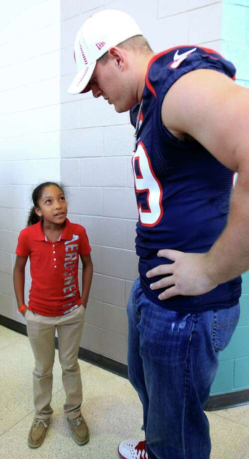 Houston Texans defensive end J. J. Watt talks with Jade Miller, 9, in a hallway after a pep rally as the Texans and the American Heart Association kicked off the NFL PLAY 60 Challenge with more than 1,000 students at Pin Oak Middle School. Photo: Karen Warren, Houston Chronicle / © 2013 Houston Chronicle