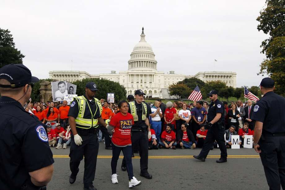 A demonstrator is arrested by U.S. Capitol Police officers on Capitol Hill during a immigration rally in Washington, on Tuesday, Oct. 8, 2013, as they press Congress to deal with immigration legislation. ( AP Photo/Jose Luis Magana) Photo: Jose Luis Magana, Associated Press