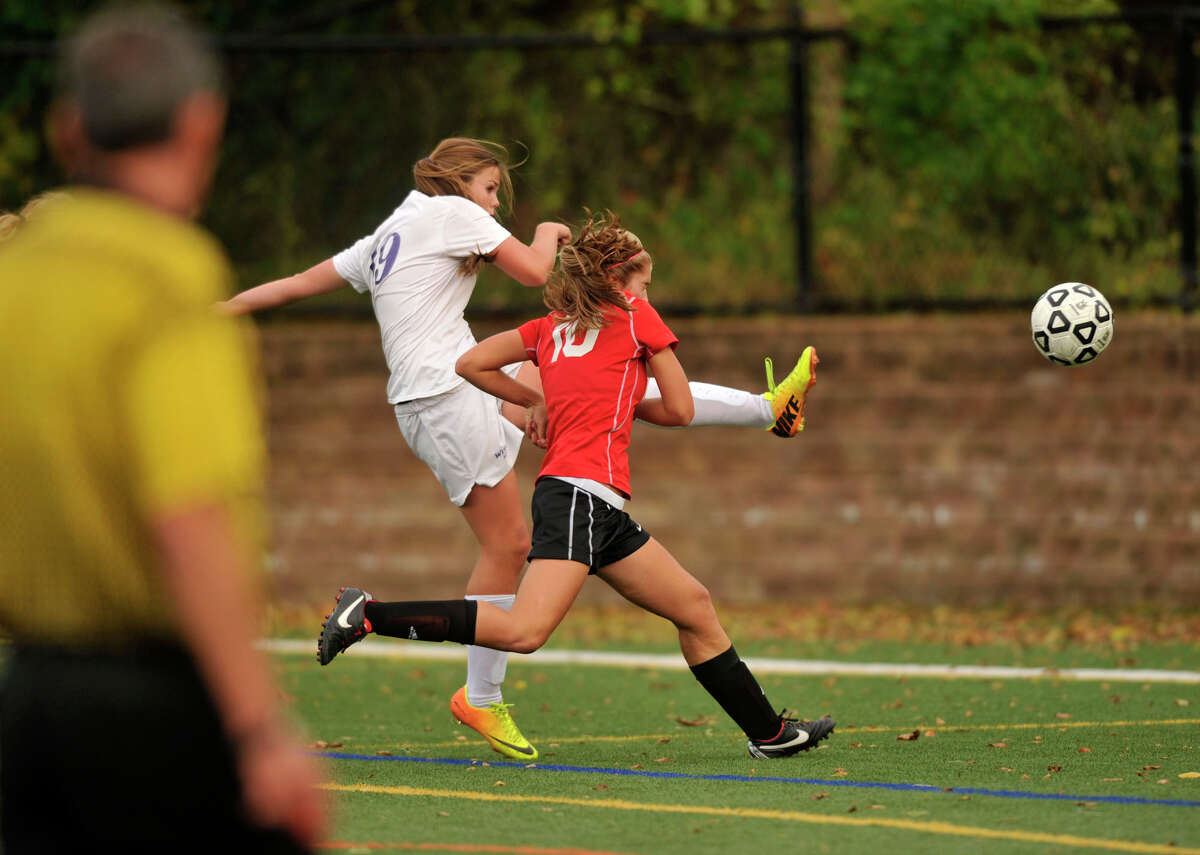 Westhill's Jess Laszlo shoots and scores while under pressure from New Canaan's Caroline Gordon during their game at Westhill High School in Stamford, Conn., on Tuesday, Oct. 8, 2013. Westhill won, 3-0.