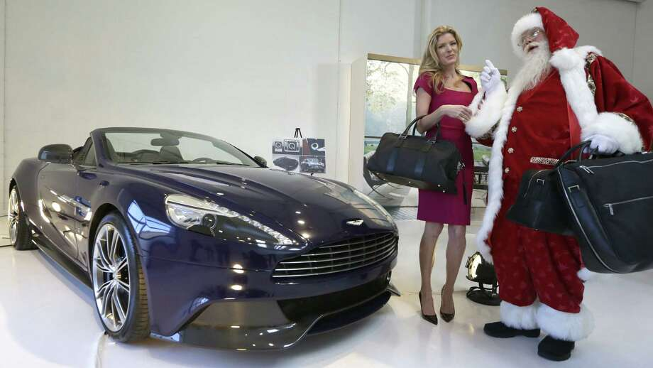 Santa Claus, portrayed by Brady White, and Lesley Heaton show off a 2014 Aston Martin Vanquish Volante, another of the fantasy gifts. Neiman Marcus will offer 10 of the cars, handmade in England in an exclusive shade of blue, for $344,500 each. Photo: Photos By LM Otero / Associated Press