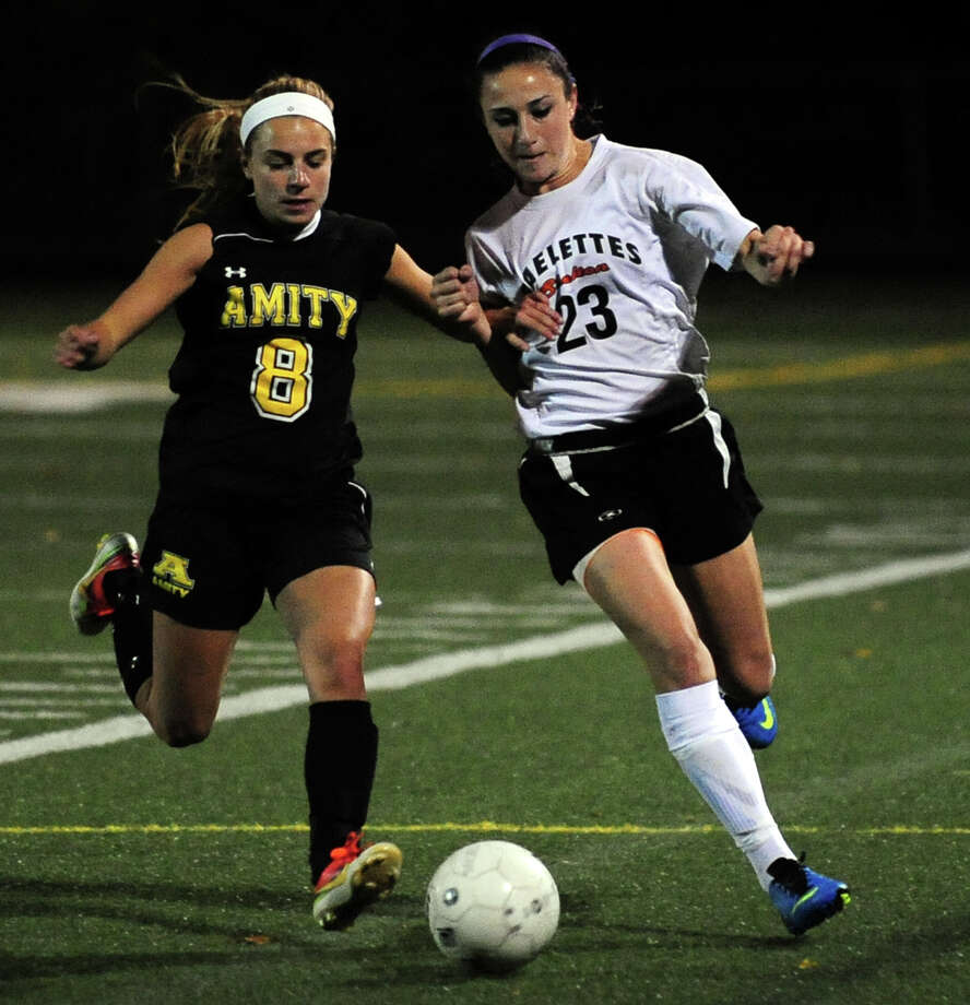 Amity's Cassie Giza, left, and Shelton's Samantha Hartmayer, chase down the ball during girls high school soccer action in Shelton, Conn. on Tuesday October 8, 2013. Photo: Christian Abraham / Connecticut Post