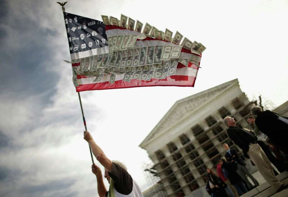 WASHINGTON, DC - OCTOBER 08:  David Barrows, of Washington, DC, waves a flag with corporate logos and fake money during a rally against money in politics outside the Supreme Court October 8, 2013 in Washington, DC. On Tuesday, the Supreme Court heard oral arguments in McCutcheon v. Federal Election Committee, a first amendment case that will determine how much money an individual can contribute directly to political campaigns.  (Photo by Chip Somodevilla/Getty Images) ORG XMIT: 183922694 Photo: Chip Somodevilla / 2013 Getty Images