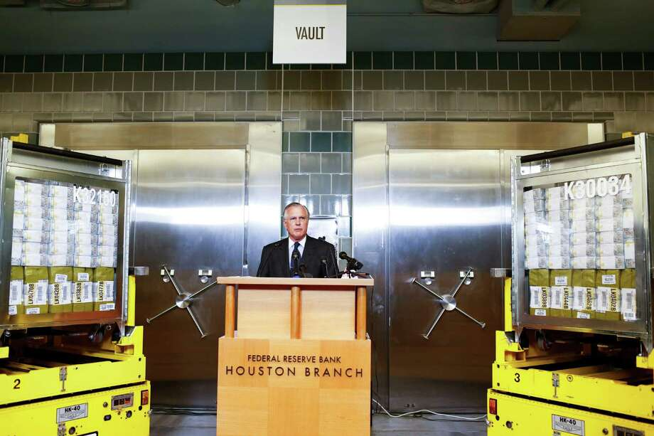 Richard Fisher, president and CEO of the Federal Reserve Bank of Dallas, introduces the newly redesigned $100 bill on Tuesday in Houston. Flanking him are automated vehicles each holding $40 million in $100 bills. Photo: Eric Kayne / ©Eric Kayne 2013