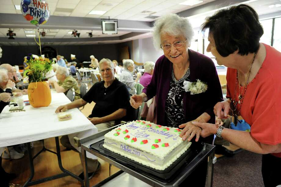 Vera Brooks, 100, second from right, has her fingers in the frosting of her birthday cake during a senior luncheon on Tuesday, Oct. 8, 2013, at Guilderland Town Hall in Guilderland, N.Y. Joining her is Senior Services volunteer Josie Geisel, right, and Vera's son, Charles Brooks, center. (Cindy Schultz / Times Union) Photo: Cindy Schultz / 00024162A
