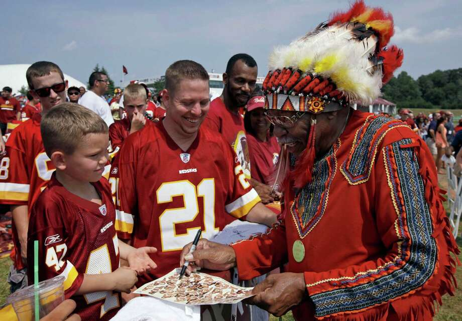 "FILE - In this Saturday, Aug. 4, 2012 file photo, Zena ""Chief Z"" Williams, unofficial mascot of the Washington Redskins, signs autographs during fan appreciation day at the Redskins' NFL football training camp at Redskins Park in Ashburn, Va. The name Washington Redskins has inspired protests, hearings, editorials, lawsuits, letters from Congress, even a presidential nudge. Yet behind the headlines, it's unclear how many Native Americans think ""Redskins"" is a racial slur. (AP Photo/Alex Brandon, File) ORG XMIT: NY113 Photo: Alex Brandon / AP"