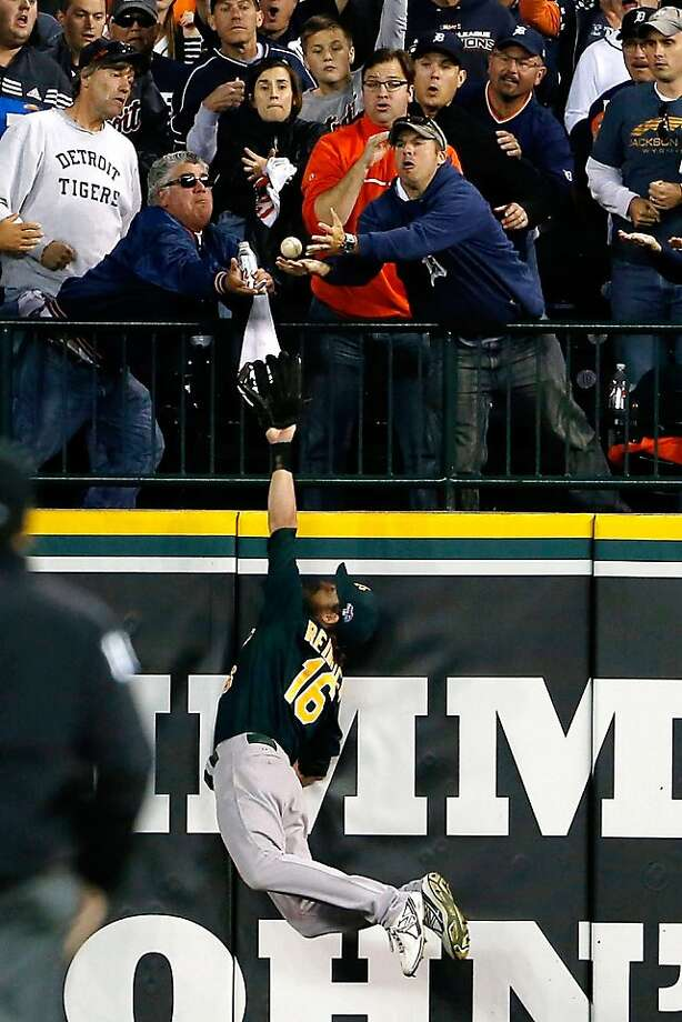A's right fielder Josh Reddick leaps for Victor Martinez's seventh-inning homer, but fans intervene before he had the opportunity to catch it. It tied the game 4-4. Photo: Mike Mulholland, Associated Press