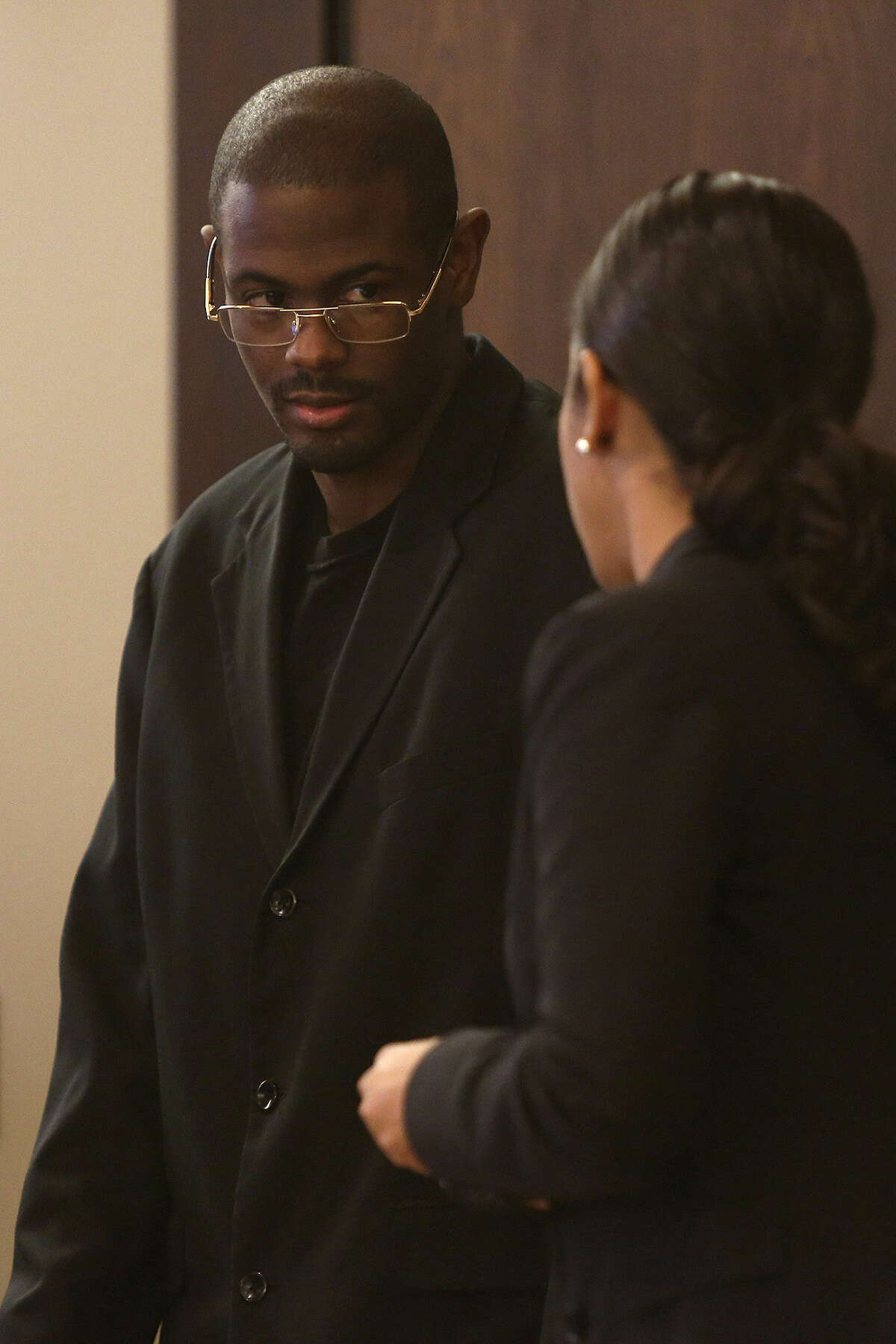 """Bernard """"B.J."""" Brown confers with his attorney, Jennifer Maritza Perez-Stewart, during his trial Tuesday for the murder of Samuel Johnson Jr."""