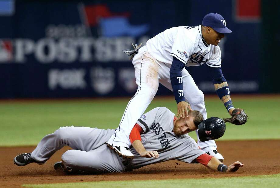 Boston Red Sox's Will Middlebrooks (16) slides under Tampa Bay Rays shortstop Yunel Escobar (11) after he was tagged out on a double play in the third inning in Game 4 of an American League baseball division series, Tuesday, Oct. 8, 2013, in St. Petersburg, Fla. (AP Photo/Mike Carlson) ORG XMIT: SPD117 Photo: Mike Carlson / FR155492 AP