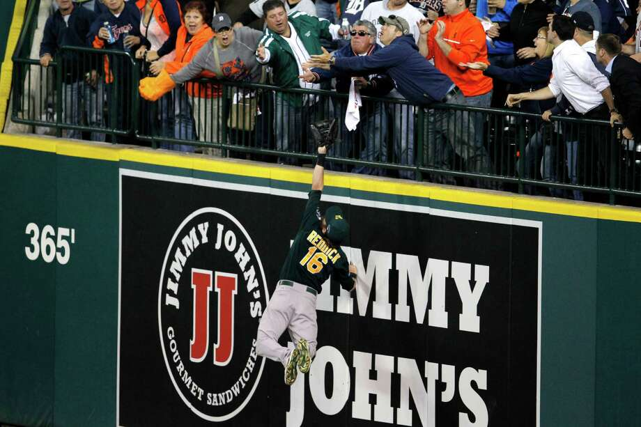 Oakland Athletics right fielder Josh Reddick stretches but is unable to catch a solo home run by Detroit Tigers' Victor Martinez, as fans reach for the ball during the seventh inning of Game 4 of baseball's American League division series in Detroit, Tuesday, Oct. 8, 2013. (AP Photo/Duane Burleson) ORG XMIT: MICO245 Photo: Duane Burleson / FR38952 AP